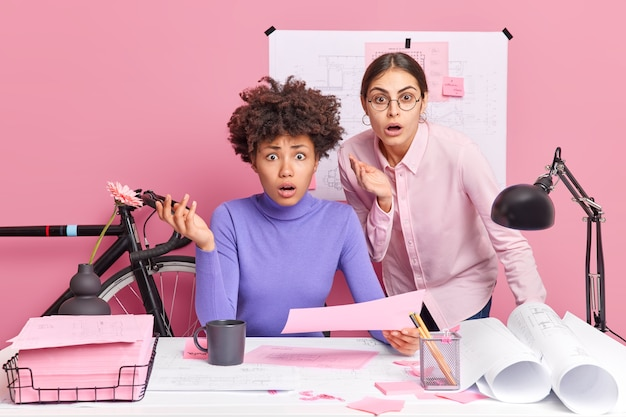 Photo of puzzled two female coworkers stare indignant, realise about deadlie have not much time to finish project work pose in coworking space
