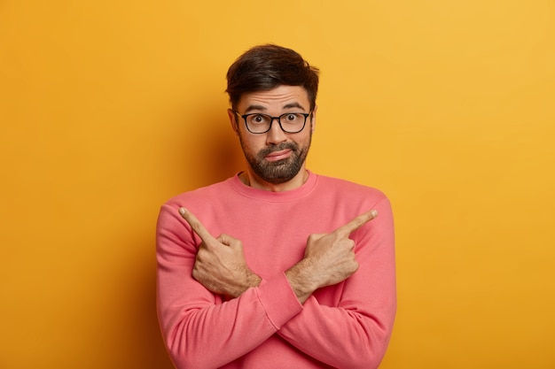Photo of puzzled unshaven man points sideways, crosses arms over chest, doubts between two choices or variants, has bewildered look, wears spectacles and rosy sweater, isolated on yellow wall.