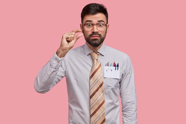 La foto di un giovane con la barba lunga perplesso fa un gesto di taglia, mostra qualcosa di minuscolo, indossa una camicia formale e una cravatta lunga, ha un'espressione sorpresa