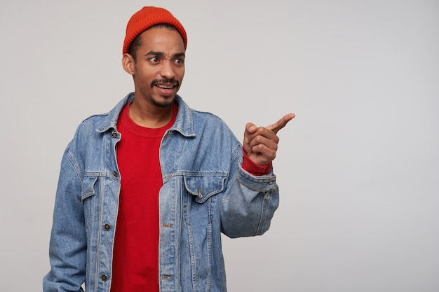 Photo of puzzled young dark skinned bearded guy frowning his eyebrows while looking aside with confused face, standing over white wall with raised forefinger