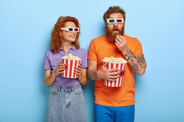 Photo of redhaired female and male couple watch movie in cinema theatre