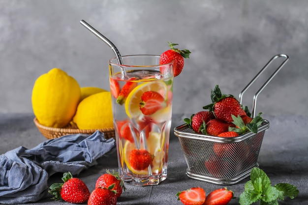 Photo of refreshing summer iced cold drink. strawberry infused waters. mineral water with fresh strawberries lemon with a grey background. detox water with strawberry lemon. copy space.