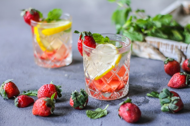 Photo of refreshing summer iced cold drink with strawberry lemon mint lemonade in glass. mineral water with fresh strawberries lemon. detox water with strawberry lemon mint. copy space. wooden box