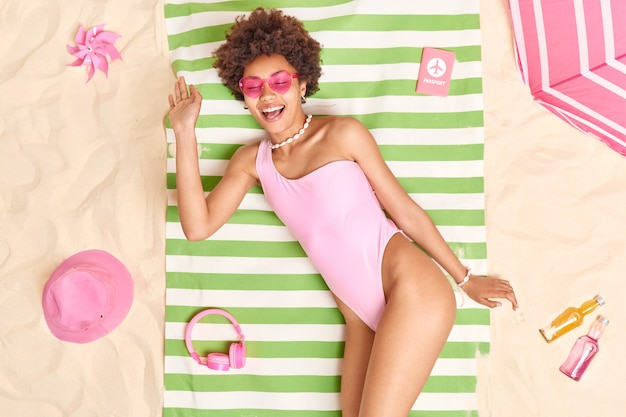 Photo of relaxed glad young afro american model smiles pleasantly wears pink sunglasses and bikini lies on green striped towel surrounded by necessary items sunbathes at beach on white sand