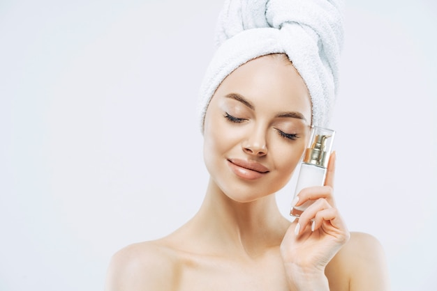 Photo of relaxed healthy young european woman stands with closed eyes, holds bottle of cosmetic product for elastic skin, poses half naked against white background.