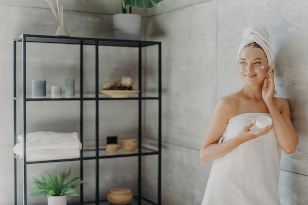 Photo of relaxed young woman applies face cream