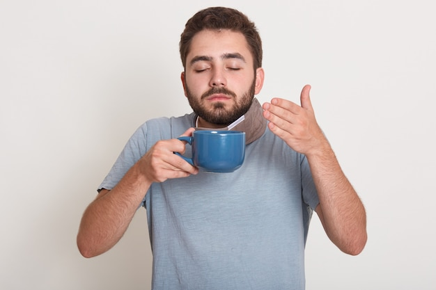 Photo of relaxing young man holding blue mug, smelling and drinking tea or coffee.