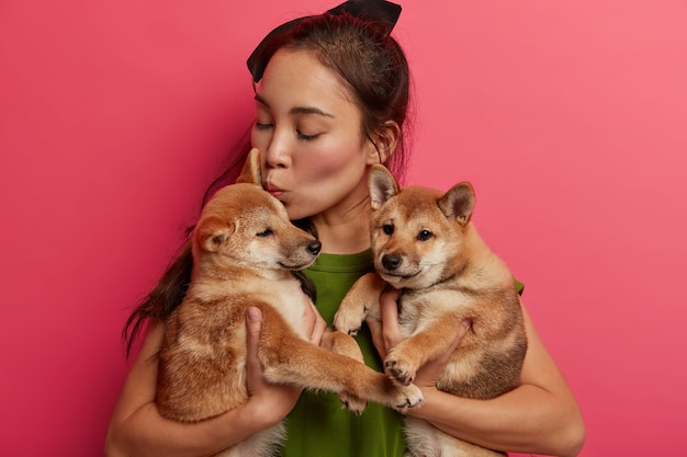 Photo of responsible female host kisses cute puppies, carries to groomer or vet, attend dog salon, have friendly relationship, poses against pink background