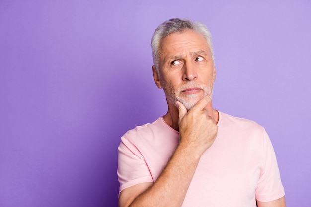 Photo of retired grandfather arm chin thoughtful look empty space wear pink t-shirt isolated purple color background
