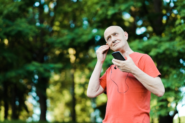 Photo of retired pensioner is wearing headphones while listening to music and trying to overhear in the park.