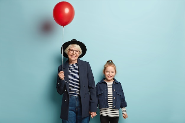Photo of retired senior woman holds hand of little adorable granddaughter, come on party, hold red balloon