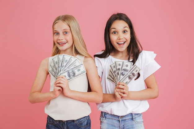 Photo of rich brunette and blonde girls 8-10 wearing casual clothing expressing surprise while holding lots of money in dollar cash, isolated over pink background