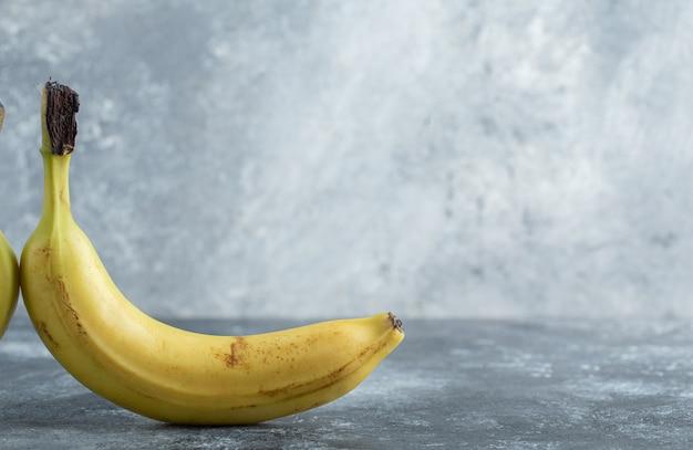 Foto di banana gialla matura su sfondo grigio.