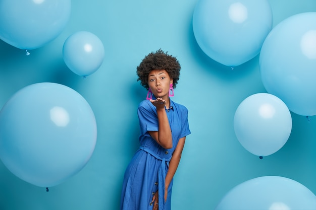 Photo of romantic curly haired woman blows kiss to lover, has party mood, dressed in pretty dress, poses against wall with balloons. blue color prevails. female enjoys her birthday party