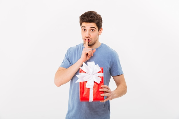 Photo of romantic man holding birthday present and asking to keep secret with finger on lips, isolated over white wall