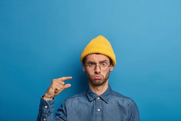 La foto di un uomo triste e dispiaciuto modella un oggetto minuscolo, mostra un oggetto piccolo, non riceve molto, vestito con un cappello giallo alla moda e una camicia di jeans