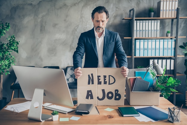 Photo of sad layoff dismissed worker mature age jobless guy carton placard poster banner search job world crisis ruined career workplace fired pack stuff modern office desktop table indoors