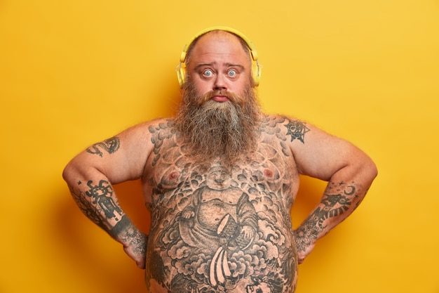 Photo of sad plump bearded man looks with surprised expression listens favorite song in headphones, keeps hands on hips, has big fat tummy, tattooed body, isolated on yellow wall