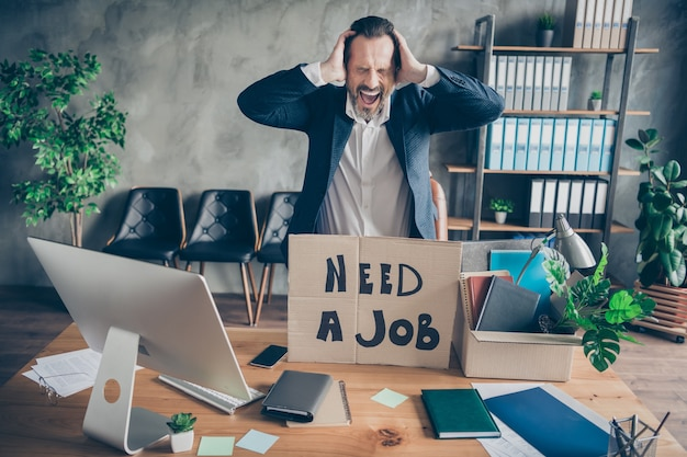Photo of sad yelling layoff dismissed worker mature guy lost job carton placard poster banner financial crisis crash career workplace fired pack stuff modern office desktop table indoors