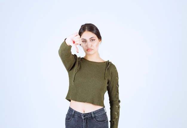 Photo of a sad young woman standing and showing a thumb down .