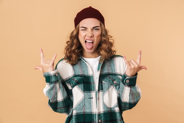 Photo of sassy young woman in knit hat winking and making horns with fingers isolated on beige