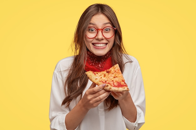 Photo of satisfied woman holds piece of pizza, feels pleased as spends free time with friends in pizzeria, looks happily directly  wears casual outfit, isolated over yellow wall. lunch