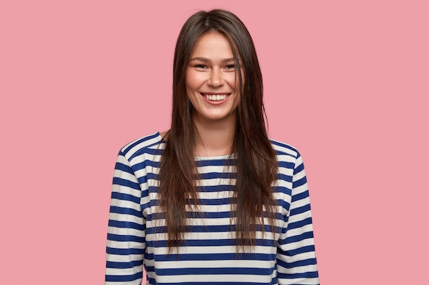 Photo of satisfied young caucasian with long dark hair, dressed in striped casual clothes, has freckled skin