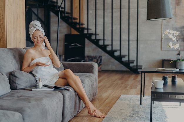 Photo of satisfied young european woman sits on comfortable sofa in living room applies face cream for reducing wrinkles wrapped in bath towel reads magazine undergoes beauty treatments at home