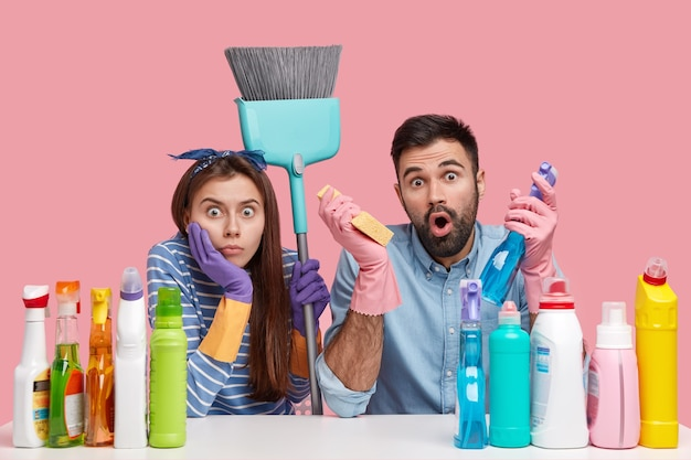 Photo of scared astonished lady and guy have surprised expressions, look with stupor, carry detergents, sponge, brush