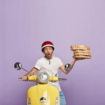 Foto del fattorino spaventato che guida il motorino giallo mentre tiene le scatole della pizza