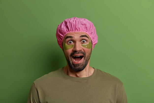Photo of scared emotional man stares with eyes popped out and screams from fear, applies collagen pads under eyes, has beauty treatments, wears protective bath hat, stands indoor. wellbeing, beauty