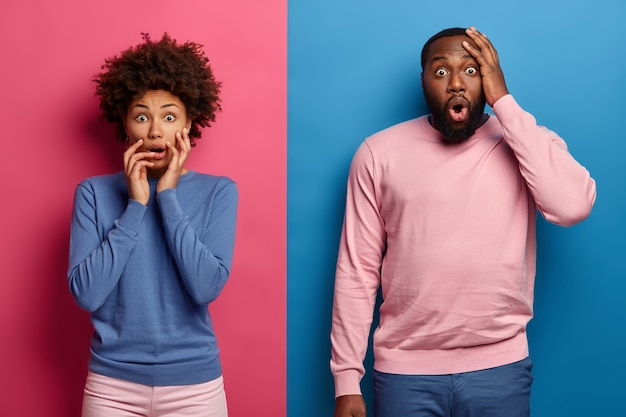 Photo of scared overwhelmed dark skinned woman and man watch horror film together, wear blue and pink clothes, tremble from fear