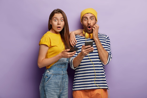 Photo of scared woman and man pose with mobile phones,shocked with astonishing news, puzzled with unexpected updates, afraid of something