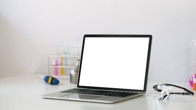 Photo of scientific experiments equipment putting on white working desk with white blank screen computer laptop. flat lay computer laptop, chemistry glassware, safety glasses.
