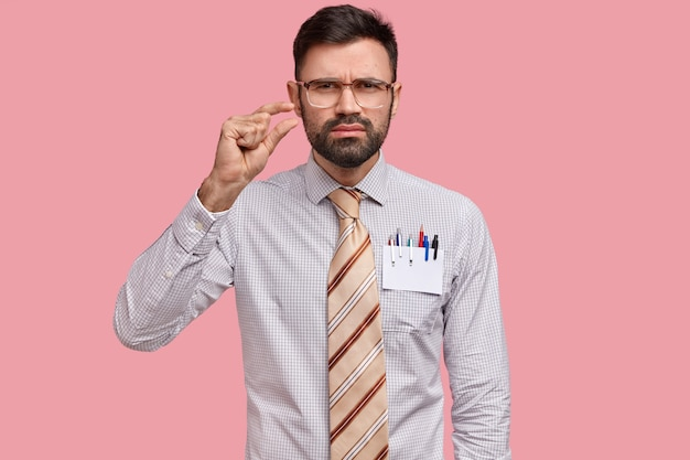 La foto di un giovane scupoloso con la barba folta, mostra qualcosa di piccolo con la mano, mostra un piccolo prestito, indossa grandi occhiali