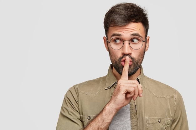 Photo of secret young man makes shush gesture, looks surprisingly aside