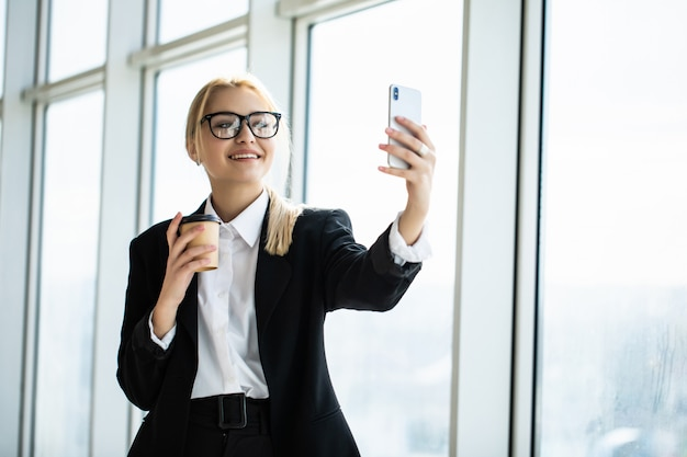 Photo of secretary woman in formal wear standing holding takeaway coffee in hand and taking selfie on mobile phone in office