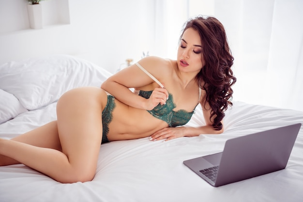 Photo of seductive remote work stripper lady online laptop show undressing on screen glam body breast take off brassiere for money customer client wear bikini sheets linen bedroom indoors