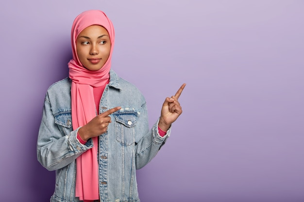 Photo of self assured arabian lady in traditional pink hijab, shows you right way, points at blank space with both fore fingers, invites going there, promots copy space. check it out with me