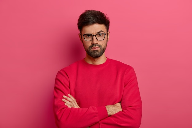 Photo of self assured man with beard, keeps arms folded over body, looks seriosly , wears casual clothes, has talk with colleague, poses indoor against pink wall. confident guy