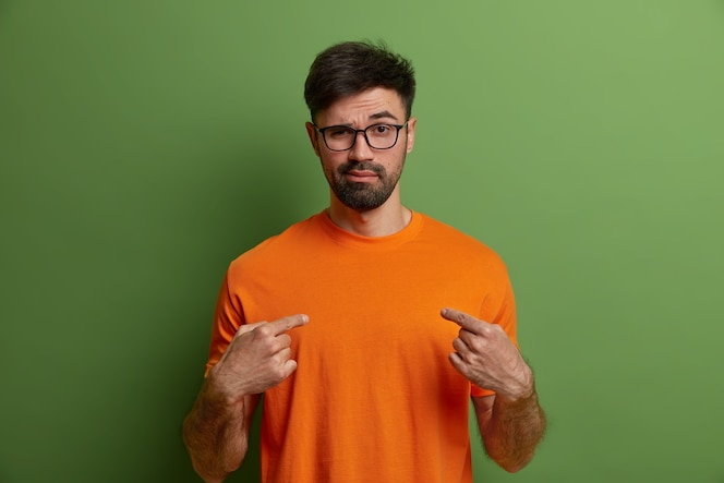 Photo of self confident cheeky sassy hipster points at himeself, says you may rely on me, wears glasses and orange t shirt, isolated on green wall. assertive arrogant bearded man indoor