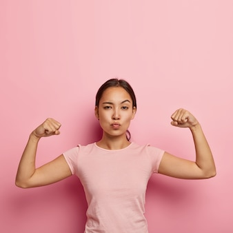 Photo of self confident serious asian girl keeps lips folded, shows her muscle and strength, wears no make up, dressed in casual t shirt, isolated on pink wall with copy space above for information