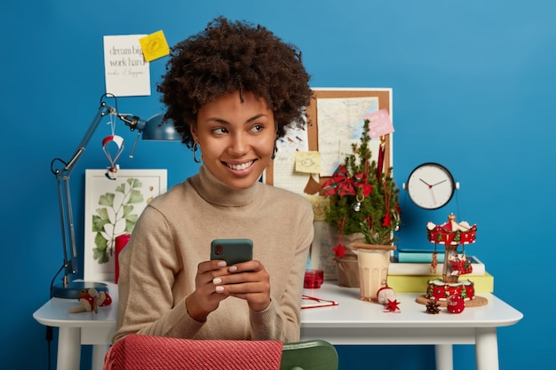 Photo of self employed ethnic woman chats online on smartphone, has break after work, sits on table near desktop, browses internet, looks with happy dreamy expression aside, blue wall.