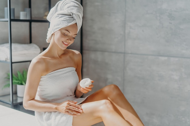 Photo of sensual young european woman uses body cream after taking bath