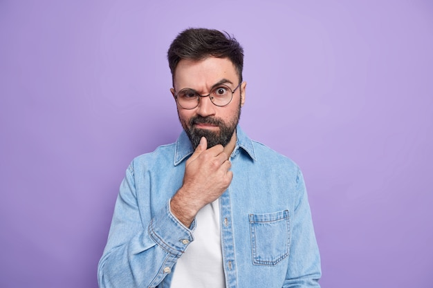 Photo of serious bearded adult man holds chin raises eyebrows frowns face dressed in fashionable shirt being dissatisfied with something