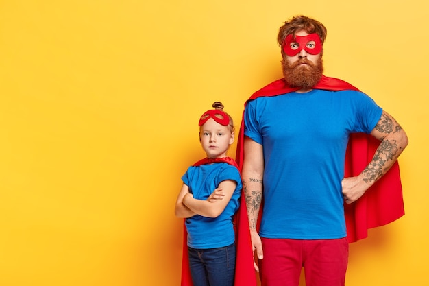 Photo of serious bearded man and self confident little child stands near with crossed arms