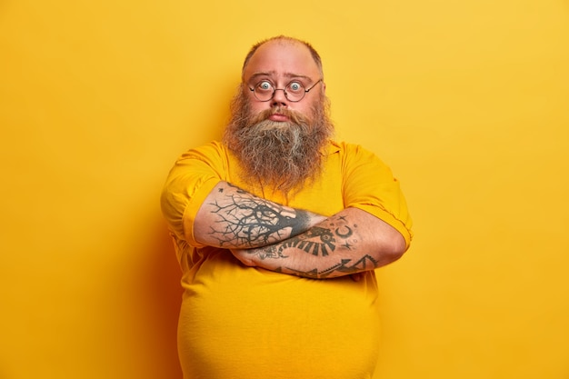 Photo of serious bearded man stands with arms folded has big beer belly, puzzled by unsuccessful dieting, has overweight because of eating wrong food, looks with surprised expression, stands indoor