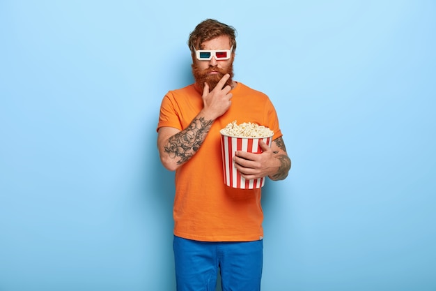 Photo of serious bearded redhead man eats popcorn