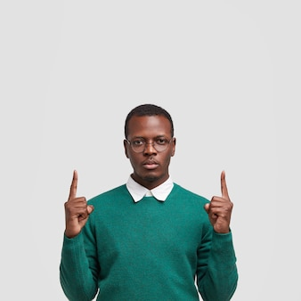 Photo of serious black man points with both index fingers upwards, shows free space above, dressed in stylish outfit