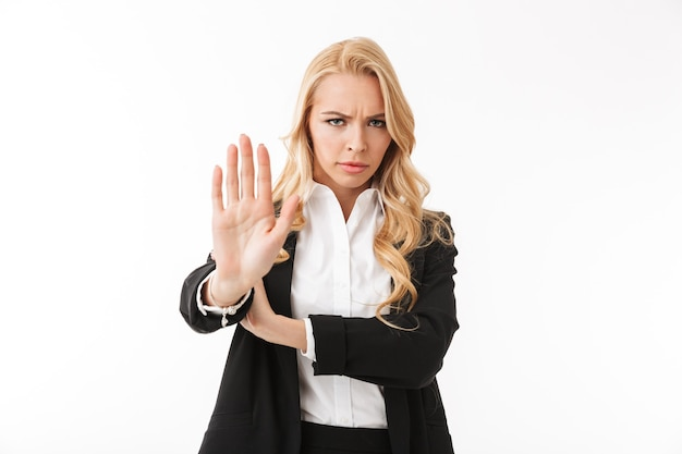 Photo of serious businesswoman wearing office suit showing palm as stop gesture, isolated